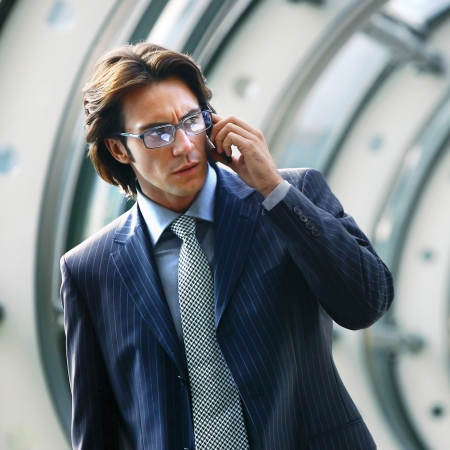 Businessman talking on mobile phone in office lobby  photo