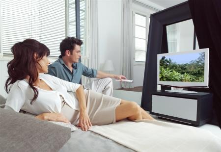 pareja viendo tv: Retrato de la joven pareja viendo la televisi�n acostado en la cama Foto de archivo