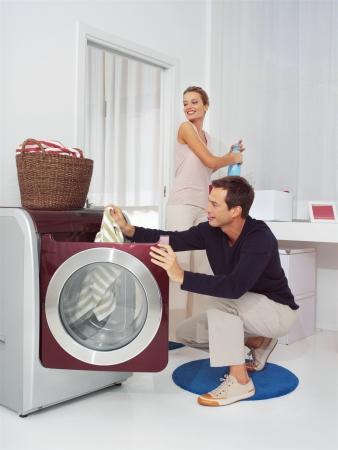 lavando ropa: El hombre pone la ropa en la lavadora