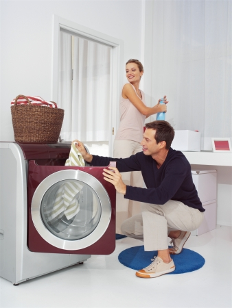 washing clothes: Man puts clothes into the washing machine
