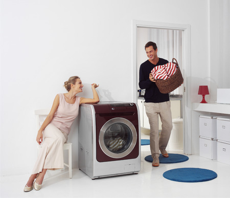 bright housekeeping: Housework, young woman and man doing laundry Stock Photo