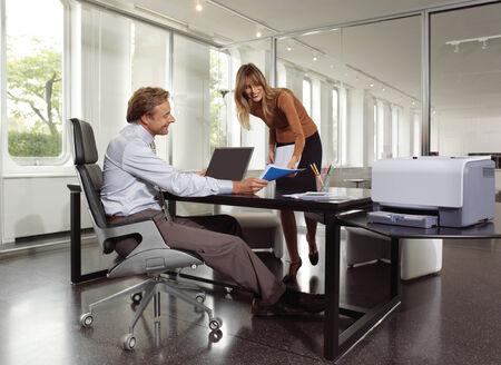 fotocopiadora: hombre de negocios y secretaria que usa máquina de copia