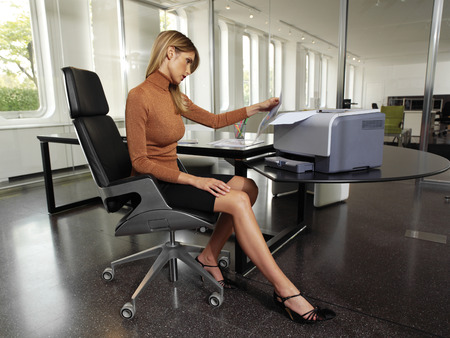 facsimile: pretty young woman using a copy machine Stock Photo