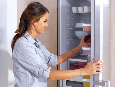 Young woman in front of the fridge Reklamní fotografie