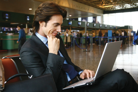 Businessman working on laptop computer at airport photo