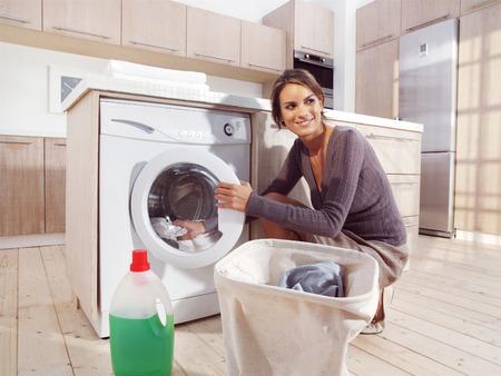 Close up of a young woman putting a cloth into washing machine