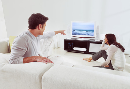 happy couple sitting on sofa and watching television together  photo