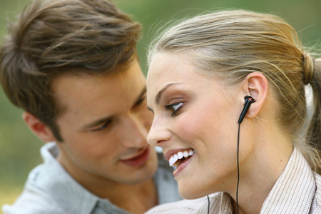 beautiful young couple listening to MP3 player  photo