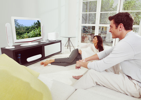 Portrait of young  happiness couple watching tv lying on bed  photo