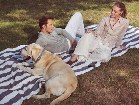 bloomy: young couple having rest with dog in bloomy garden