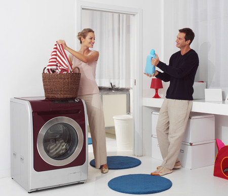 smiling woman with man dooing  laundry with washing machine  photo