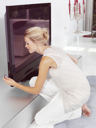 Beautiful blond woman sitting near tv and tries to connect compact chip Reklamní fotografie