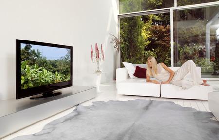 beautiful blonde woman watching TV at home photo