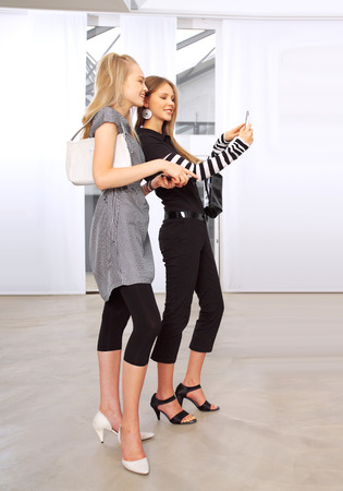 helpmate: happy girl friend with mobile phones at an exhibition  Stock Photo