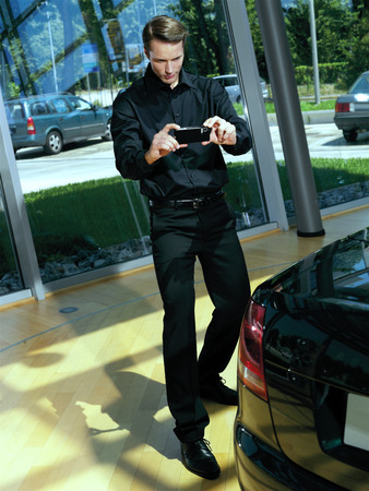 press agent: photographer in action with camera in automobile show Stock Photo