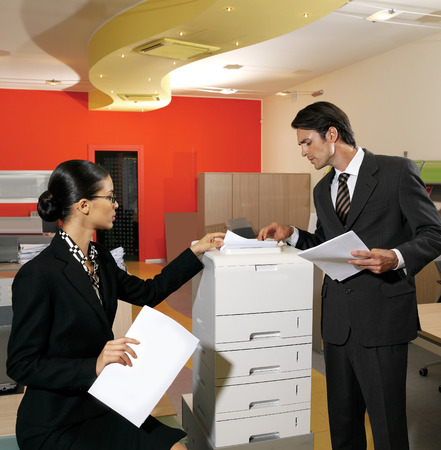 young businesswoman making copies on the photocopy machine at the office photo