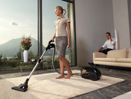 housewife with vacuum cleaner in a room