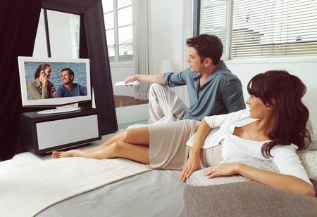 pareja viendo television: Feliz pareja joven viendo la televisión juntos en casa