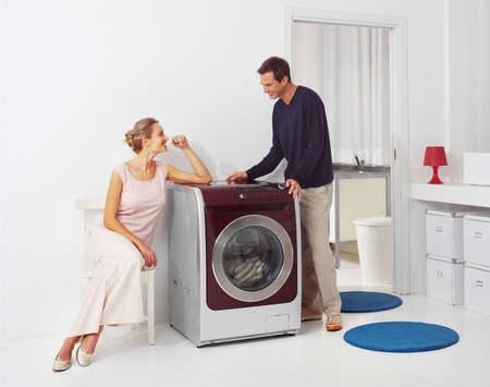 doing laundry: Housework, young woman and man doing laundry at home