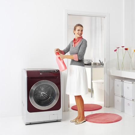 lavanderia: ama de casa mantiene detergente cerca de la lavadora en el lavadero Foto de archivo