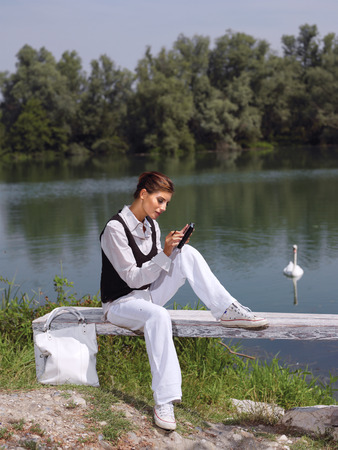 ady: Beautiful young woman using PDA outdoors