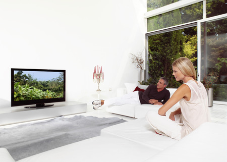 tv home: Beautiful Couple Sitting On Couch Watching TV Stock Photo