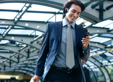 happy businessman talking on mobile phone in airport photo
