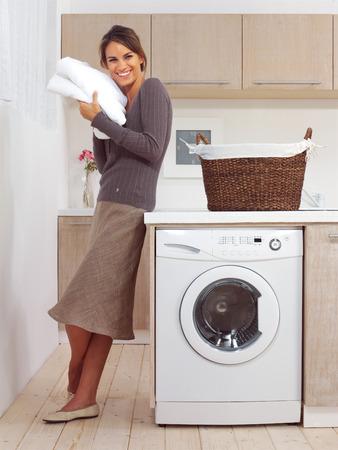 detersivi: bella ragazza sorridente in lavanderia l