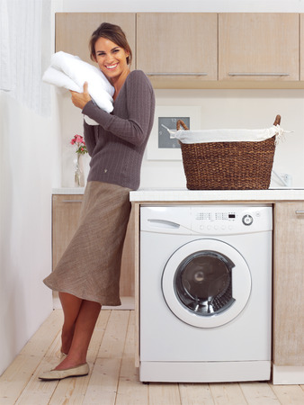 pretty smiling girl in the laundry room l photo
