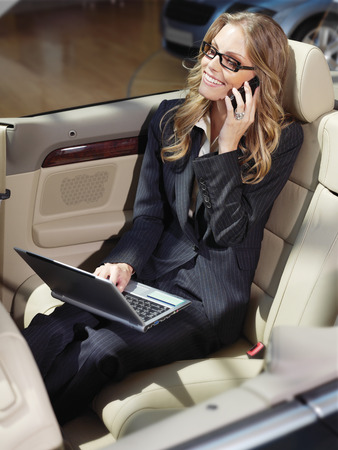 business travel, busy businesswoman with laptop in car photo