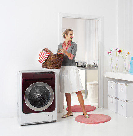 woman doing a housework holding basket of laundry  Stock Photo
