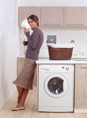 woman enjoys a smell of the washed things in laundry room  Stock Photo