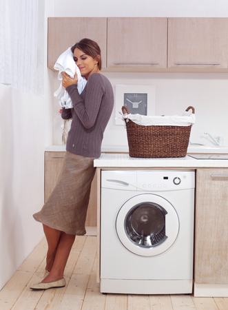 clean clothes: woman enjoys a smell of the washed things in laundry room  Stock Photo