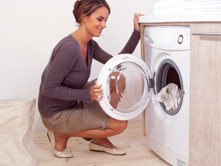Housework, young woman doing laundry