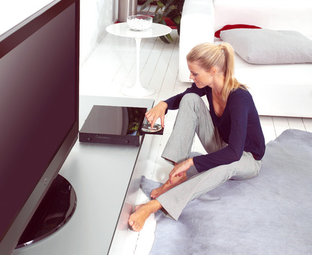 woman using dvd player in her flat Stock Photo