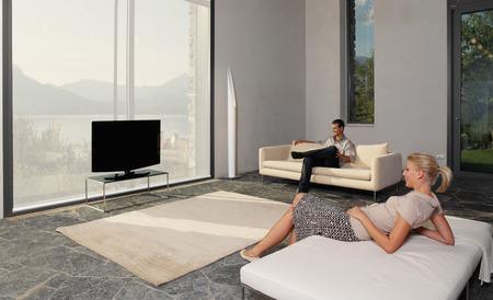 Portrait of young  happiness couple watching tv lying on sofa