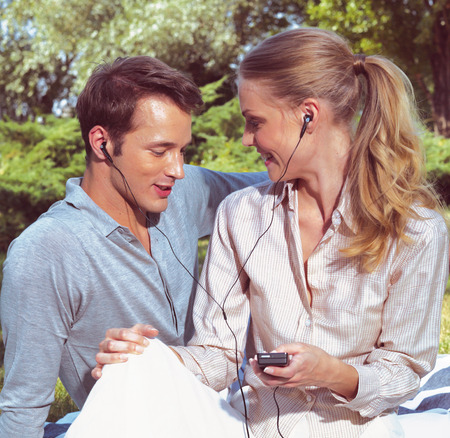 young couple smiling: beautiful young couple listening to MP3 player  Stock Photo