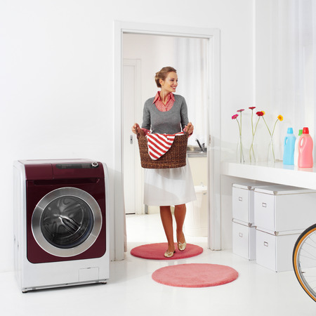 hamper: woman doing a housework holding basket of laundry  Stock Photo