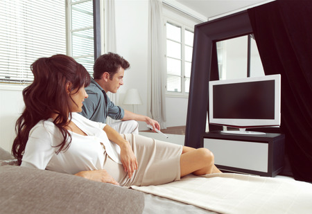 happy couple sitting on couch and watching television together photo