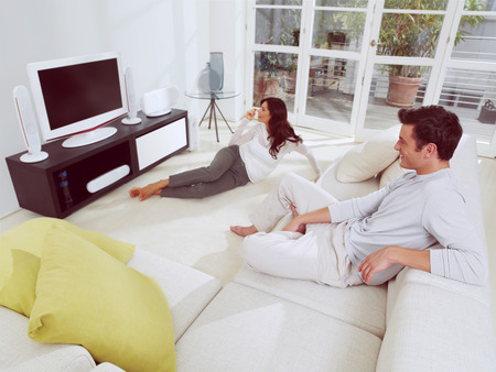 happy mature couple sitting on couch and watching television together photo