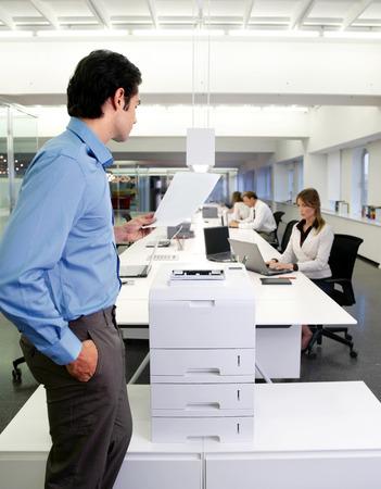 impresora: trabajador joven que usa una máquina de copia en la oficina Foto de archivo