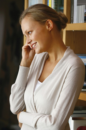 Businesswoman with cellphone while talking on smart phone photo