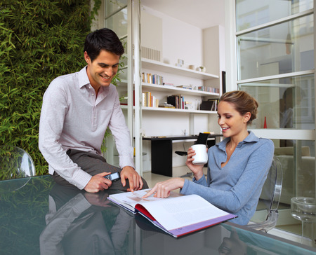 outworking: Happy young casual couple sitting at desk working together at home Stock Photo