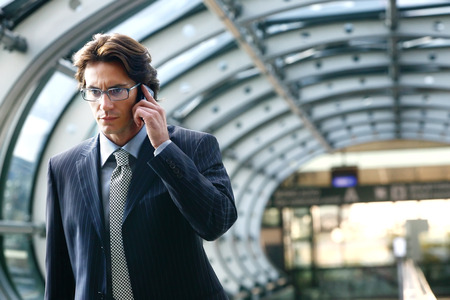 businessman waiting call: Businessman talking on mobile phone in airport Stock Photo