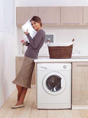 laundry room: pretty smiling woman in the laundry room Stock Photo