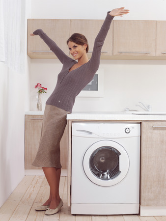 Laundry room: pretty smiling woman in the laundry room