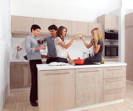 Group of friends preparing dinner in home kitchen Reklamní fotografie