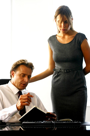 Boss helping secretary to type document correctly at meeting photo