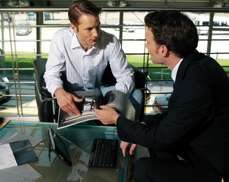 Group of young business people sitting around table on office terrace