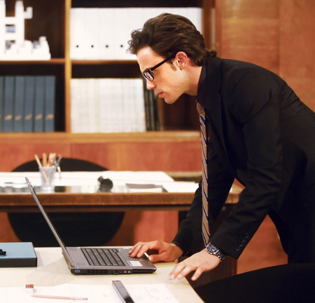 Portrait of businessman with laptop at modernoffice